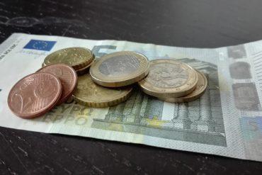 Fünf-Euro-Schein mit Kleingeld auf dem Tisch