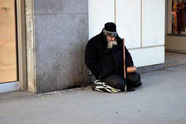 Obdachloser sitzt auf dem Boden