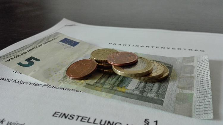 Fünf-Euro-Schein mit Kleingeld und Praktikumsvertrag