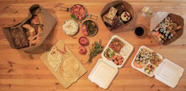 Sushi-Rollen, frisches Obst, Backwaren und anderes Essen auf einem Tisch